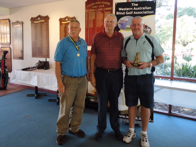 a photo of Stephen Mitchell being presented his trophy by John White. Chris Roberts is the caddy.