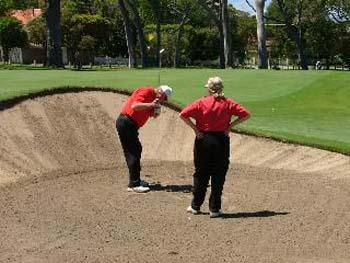 Blind Golfer and Caddy chipping out of a bunker